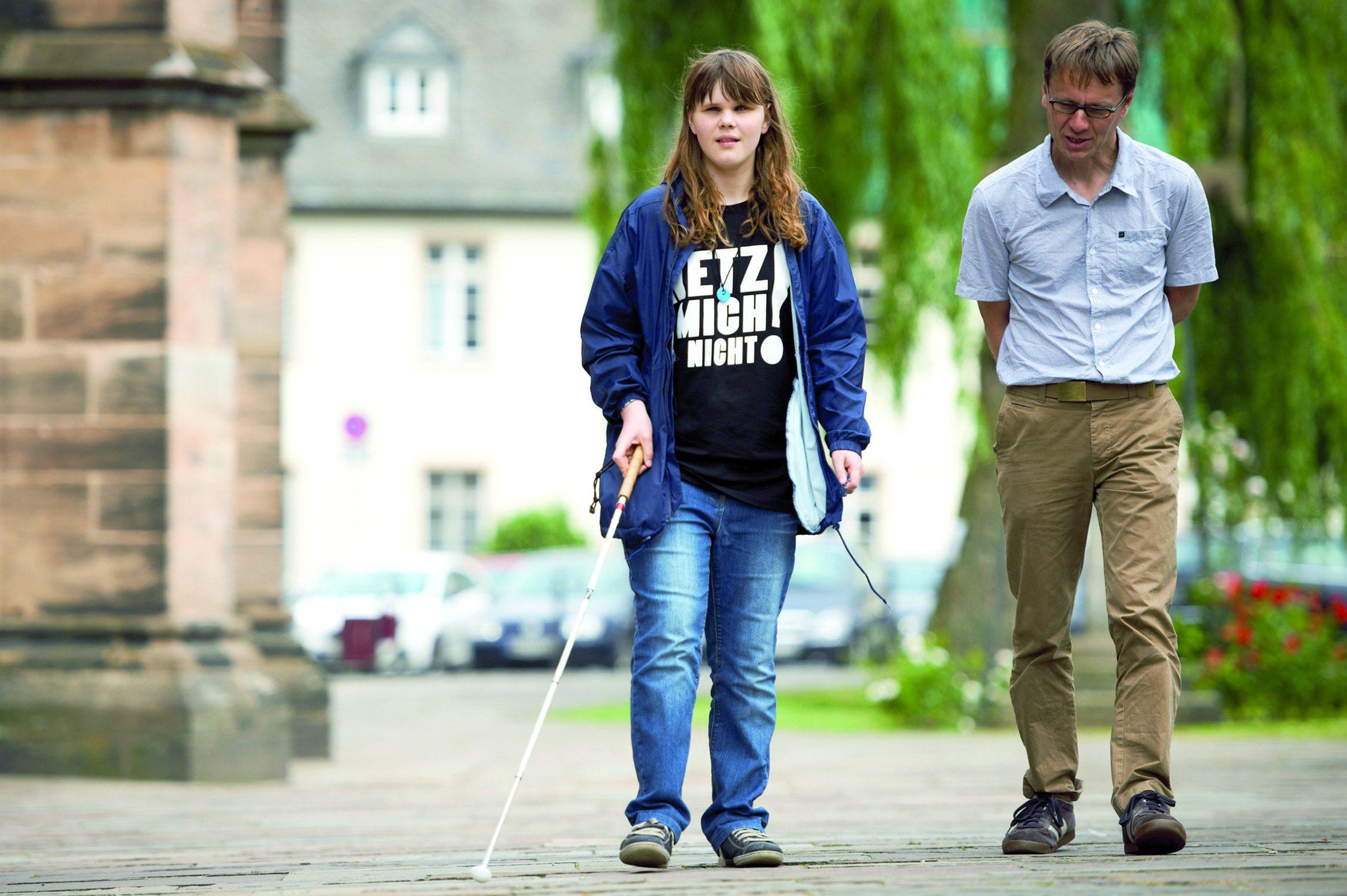 """Szene aus dem Mobilitätsunterricht: Eine männliche Fachkraft für Blinden- und Sehbehindertenrehabilitation begleitet eine junge Frau mit Blindenlangstock. Sie trägt ein T-Shirt mit der Aufschrift """"Hetz mich nicht!"""""""
