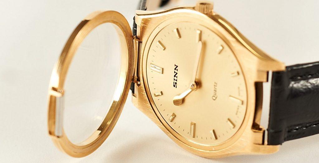 Nahaufnahme einer taktilen Armbanduhr mit goldenem Ziffernblatt und schwarzem Armband.
