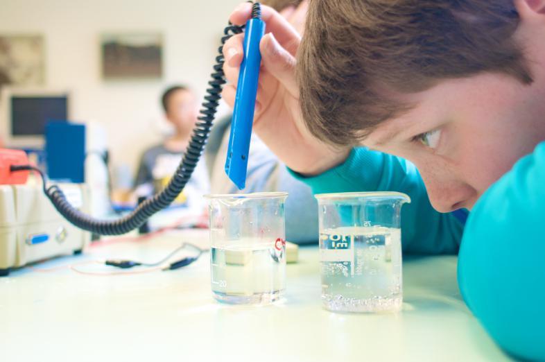 Ein junger Schüler füllt eine Flüssigkeit mit einer Pipette in einen Behälter. Szene aus dem Chemieunterricht.