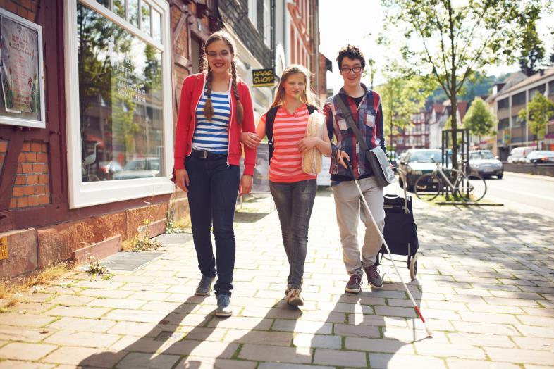 Zwei junge Mädels und ein Junge laufen Arm in Arm durch die Stadt
